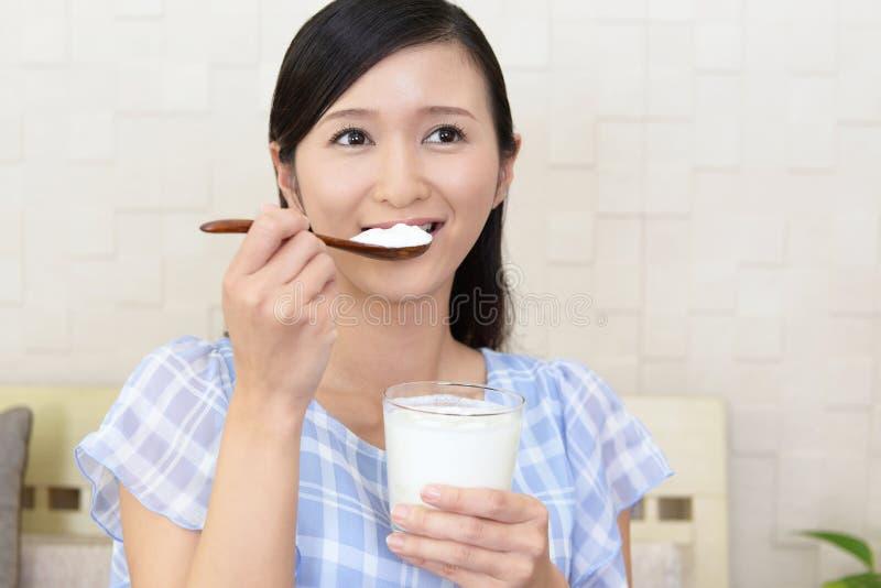 Woman who eats yogurt royalty free stock image