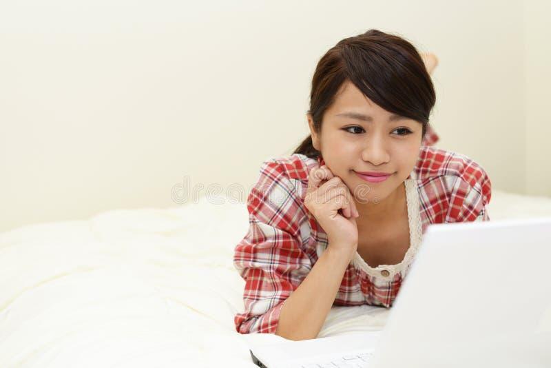 Woman in pajamas. Woman who enjoy the laptop computer royalty free stock photos