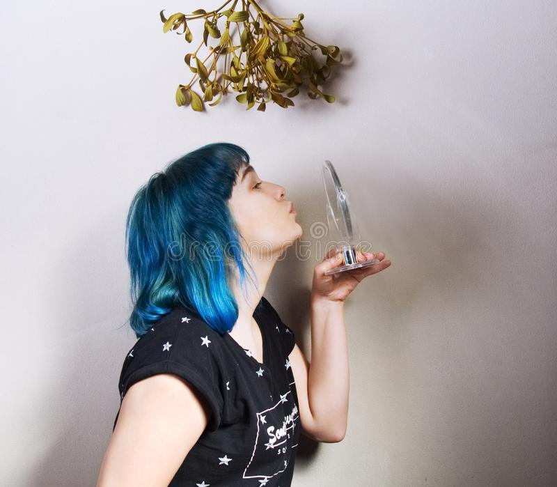 A woman who loves herself kisses the mirror standing under the mistletoe. A woman with blue hair who loves herself kisses the mirror standing under the royalty free stock photo