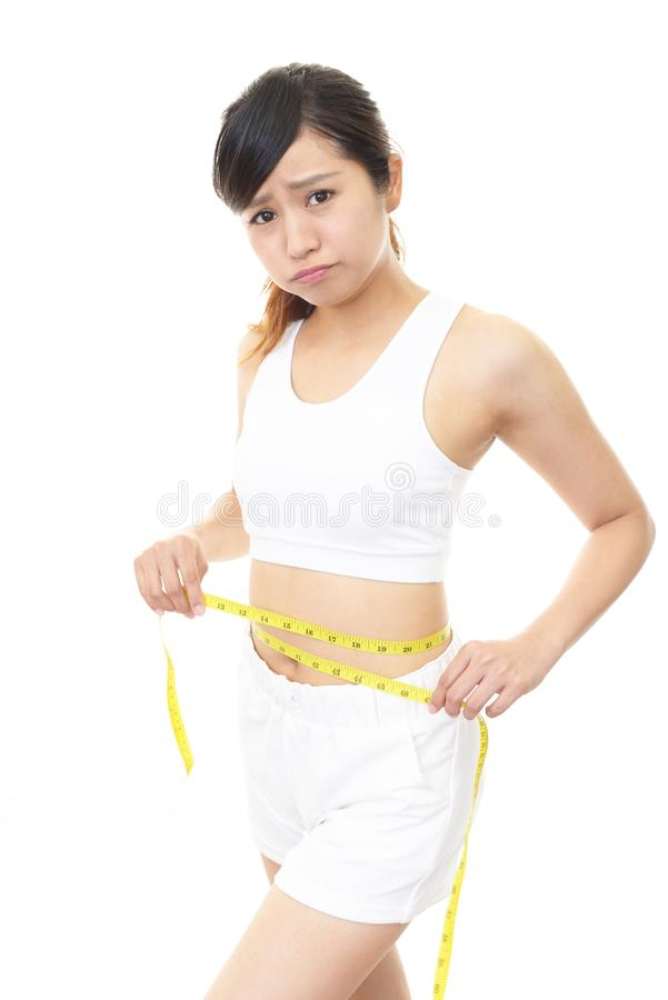 Asian young woman on diet. Woman who is measuring her waist royalty free stock photo