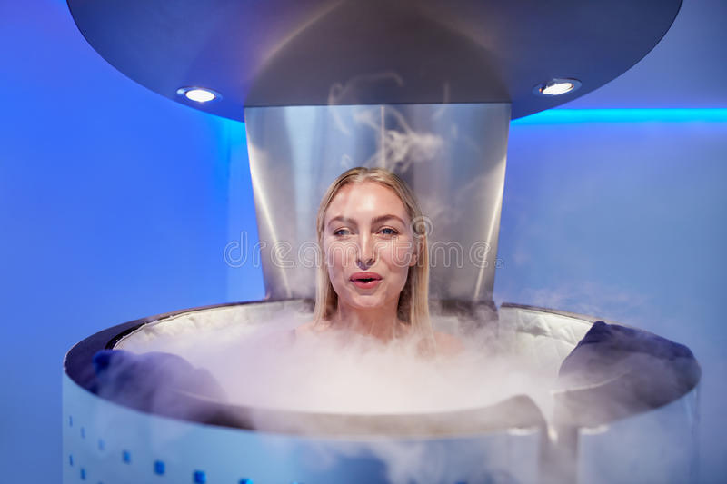 Woman in a whole body cryotherapy cabin. Portrait of happy young woman in a whole body cryotherapy cabin. She is looking at camera and smiling royalty free stock photography