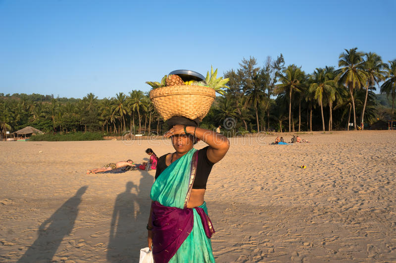 A woman with a wicker basket on his head selling fruit on the beach, India, Gokarna. stock photo