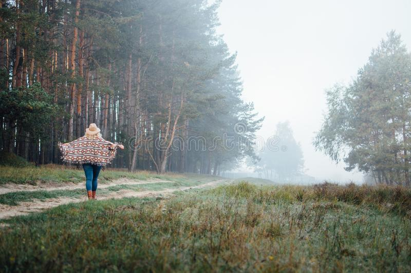 Woman in wide-brimmed felt hat and authentic poncho going along the pine tree forest at foggy morning. Woman in wide-brimmed felt hat and authentic poncho going stock image