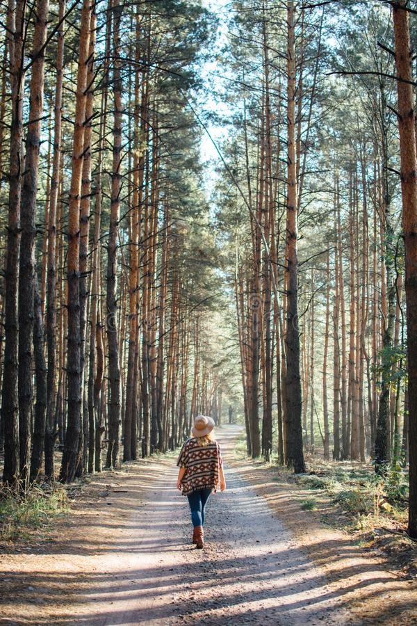 Woman in wide-brimmed felt hat and authentic poncho standing on a dirt road in foggy pine tree forest. Vertical orientation royalty free stock photo