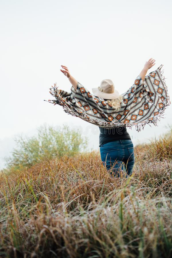 Woman in wide-brimmed felt hat and authentic poncho standing in high brown grass at foggy morning. Vertical orientation royalty free stock image