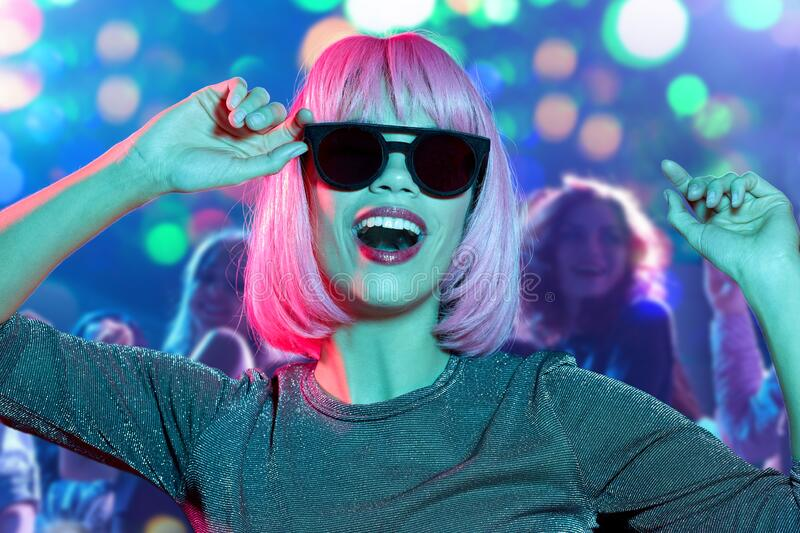 Woman in wig and sunglasses dancing at nightclub royalty free stock photos