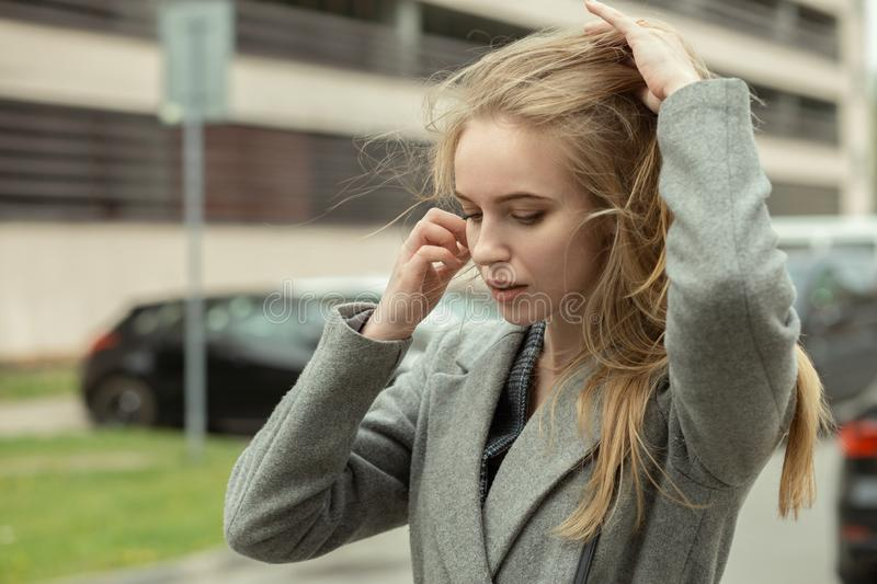 Woman at wind. Sad blond young woman with long hair at wind royalty free stock images