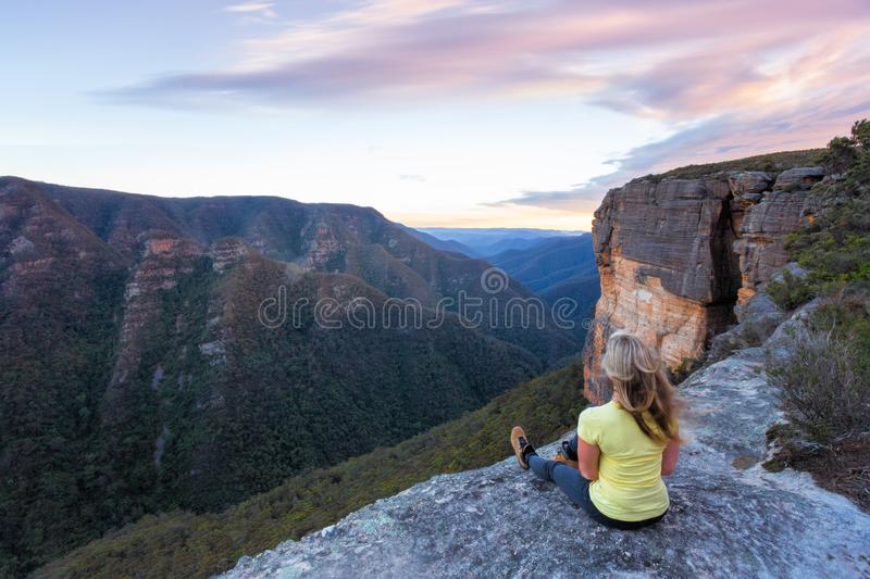 Woman with wind swept hair sitting  on edge of cliffs. Woman with long blonde wind swept hair sitting on the edge of the mountain cliffs looking out over the stock images