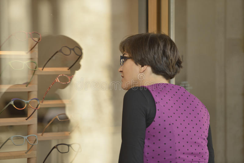 Woman window shopping spectacles, Milan stock photography