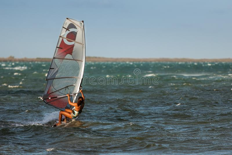 Windsurf in the lagoon. Woman windsurfing in the lagoon, acrobatic, action, active, aquatic, athletic, beach, beautiful, board, dynamic, exotic, extreme, female stock photo