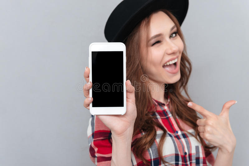 Woman winking and pointing finger at blank mobile phone screen royalty free stock images