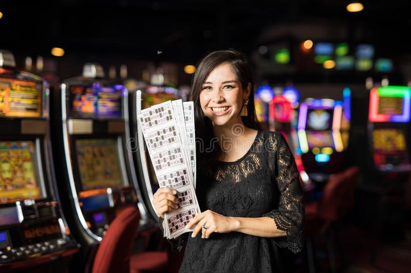 Woman winning the casino lottery. Beautiful young woman holding a bunch of lottery and bingo tickets after winning, with slot machines in the background royalty free stock photos