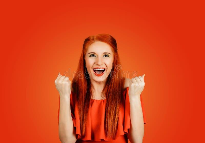 Woman winning, fist pumped, celebrating success. Happy successful student, euphoric woman winning, fist pumped, celebrating success isolated on Red background stock photography