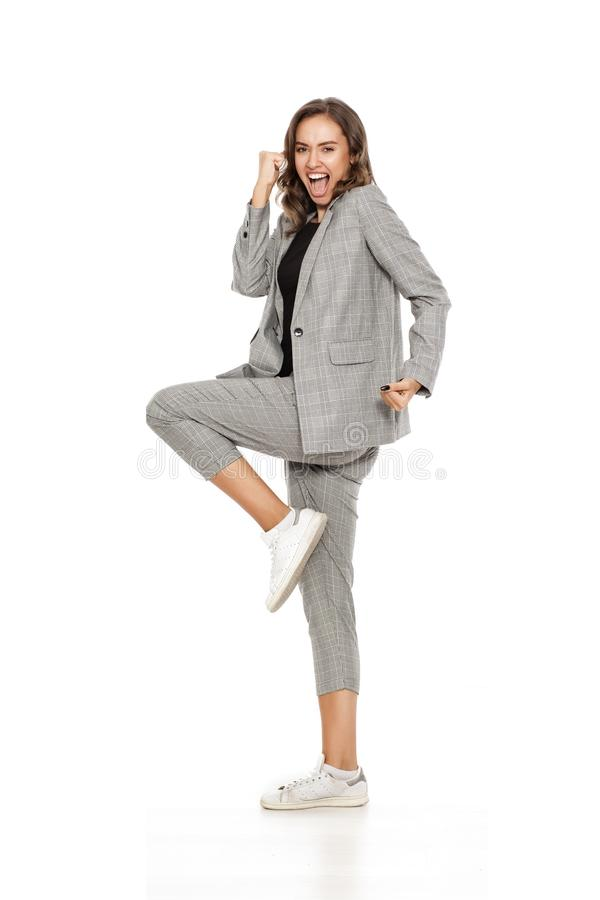 Woman with winning gesture. Young beautiful woman in casual women`s suit and white sneakers making winning gesture on a white background stock photo