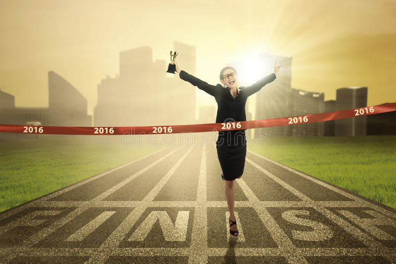 Woman winning the race competition. Photo of young business woman winning the race competition and crossing the finish line while carrying a trophy royalty free stock photography
