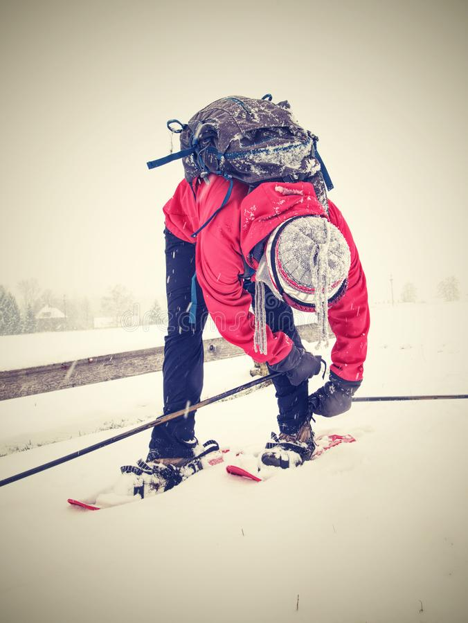 Woman on winter adventure trip on snowshoes in fresh snow. Nice woman on a winter adventure trip on snowshoes. Fresh powder snow is falling from dark sky stock image