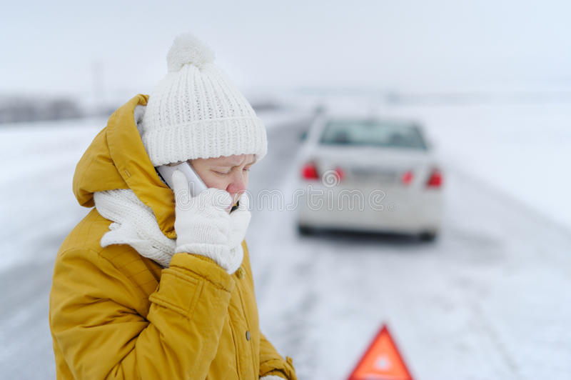 A woman in winter calls to the emergency services. stock image