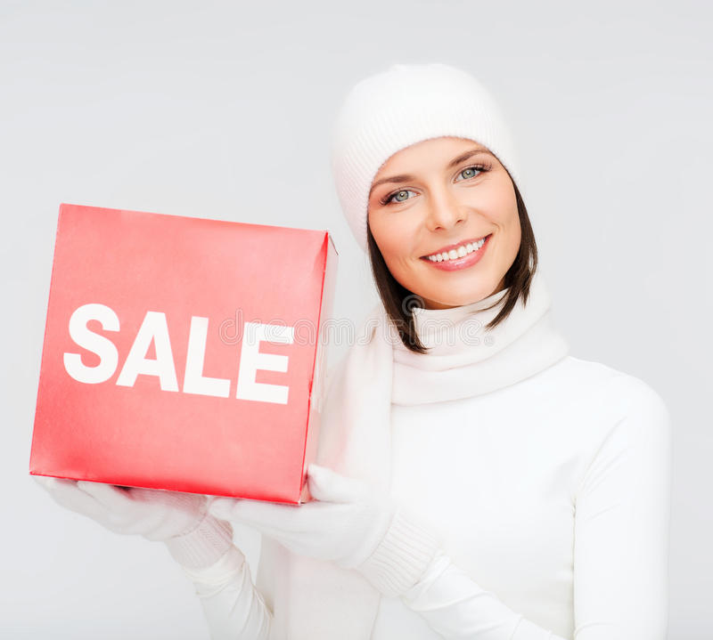 Woman in winter clothes with red sale sign. Shopping, gifts, christmas, x-mas concept - smiling woman in winter clothes with red sale sign stock photo