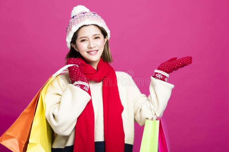 Woman in winter clothes and shopping for christmas gifts stock image