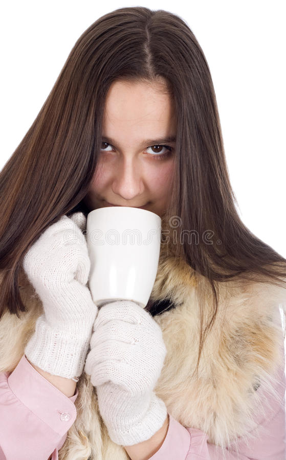 Woman in winter clothes and white gloves, drinking tea and warmed royalty free stock photos