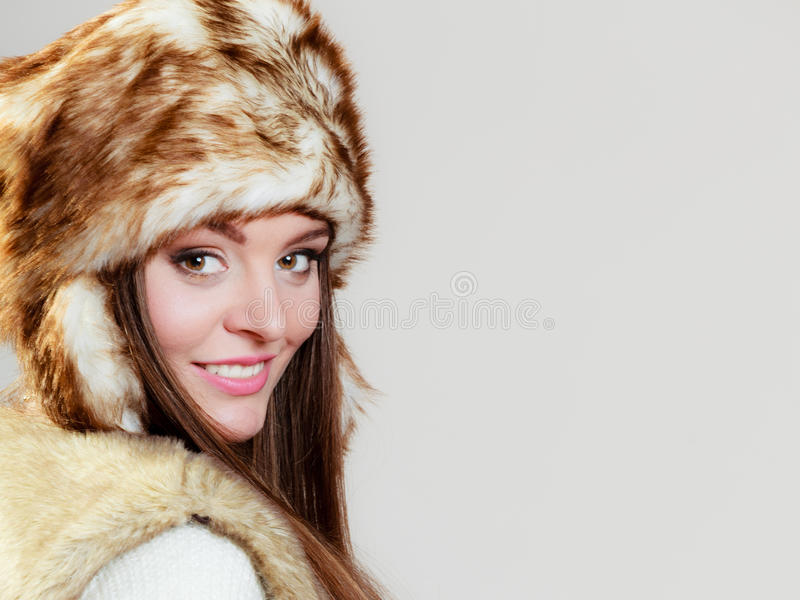 Woman in winter clothing fur cap. Winter fashion. Happy young woman wearing fashionable wintertime clothes fur cap studio shot on gray background royalty free stock photography
