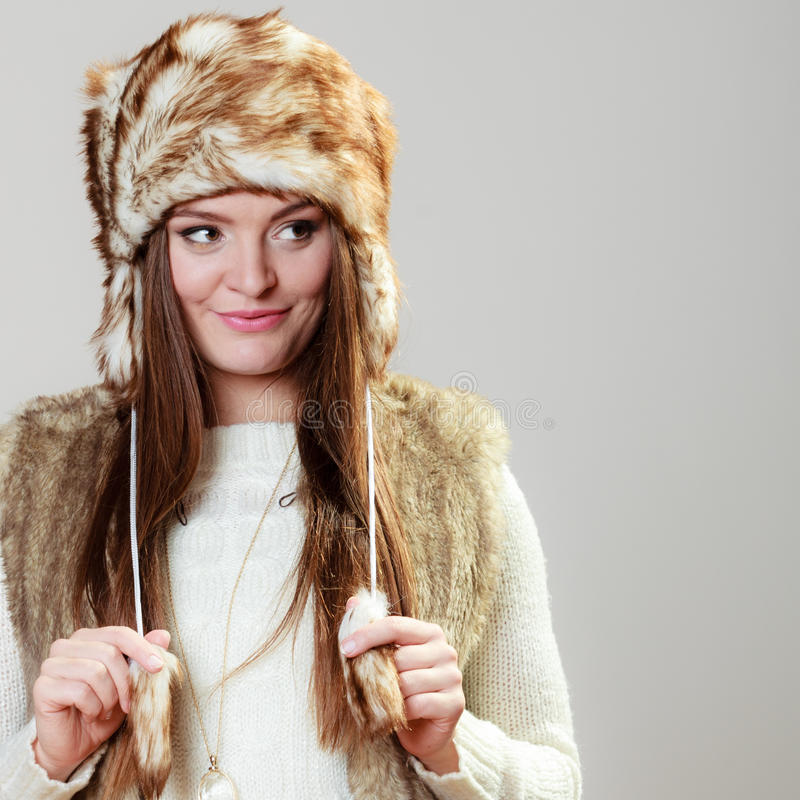 Woman in winter clothing fur cap. Winter fashion. Happy young woman wearing fashionable wintertime clothes fur cap studio shot on gray background royalty free stock photos