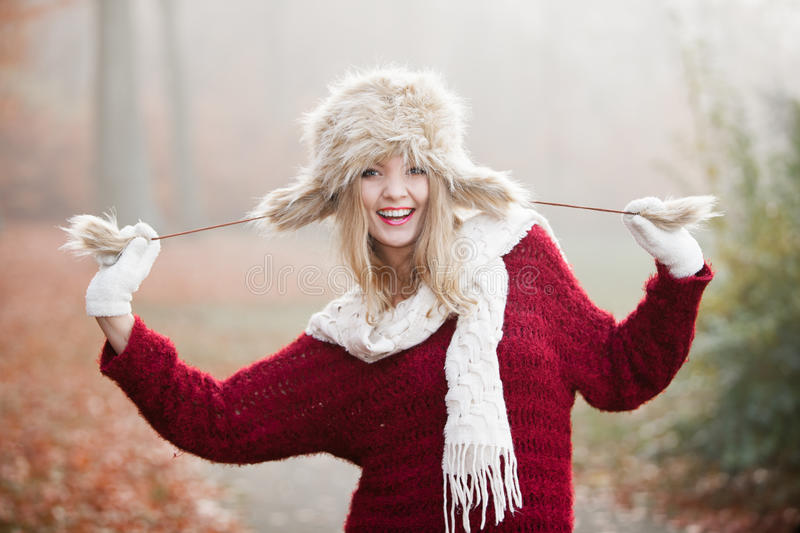 Woman in winter clothing fur cap outdoor. Winter fashion. Closeup smiling young woman wearing fashionable wintertime clothes fur cap outdoor portrait stock photos