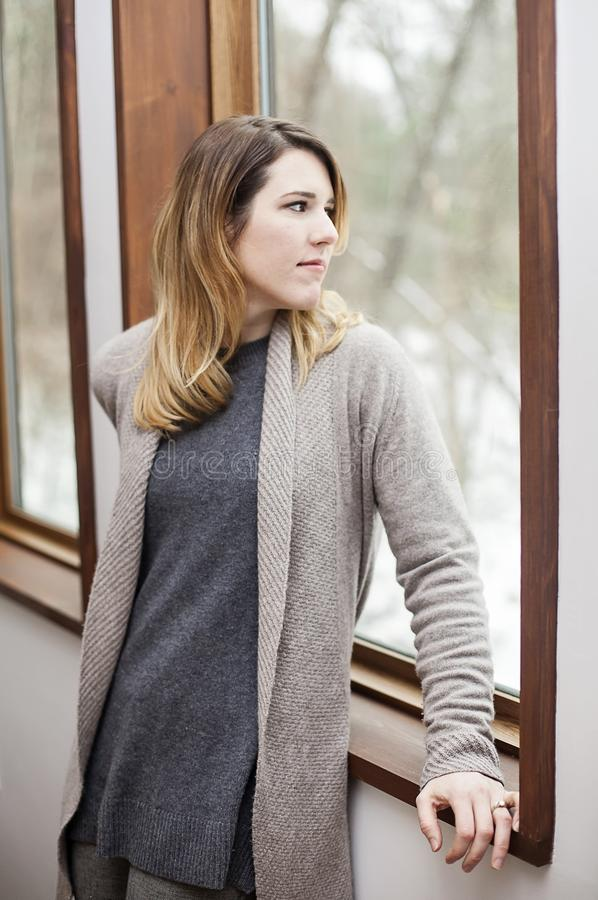 Woman with winter depression looking out window. A sad young woman wearing a sweater looking out window at home in winter stock photography