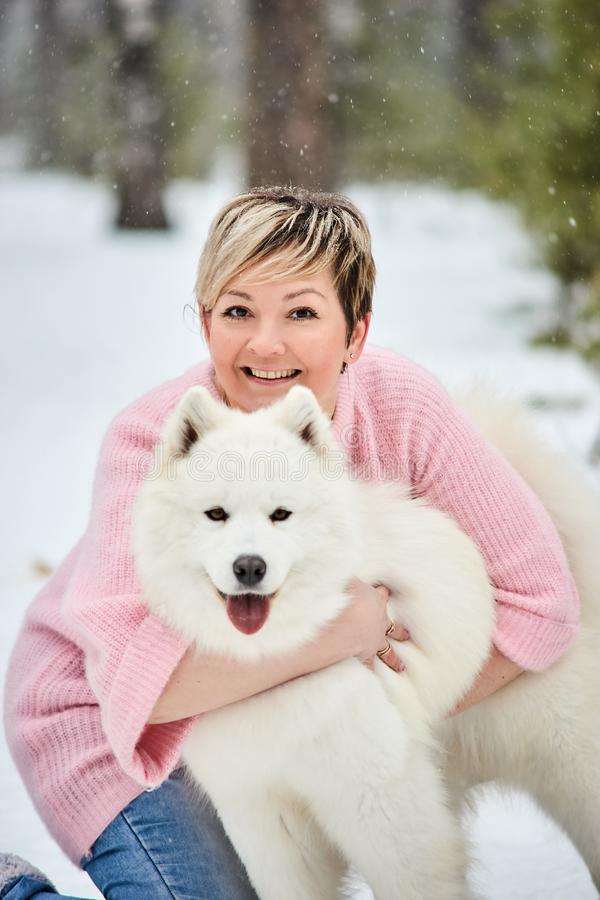 Woman in the winter forest walking with a dog. Snow is falling royalty free stock image
