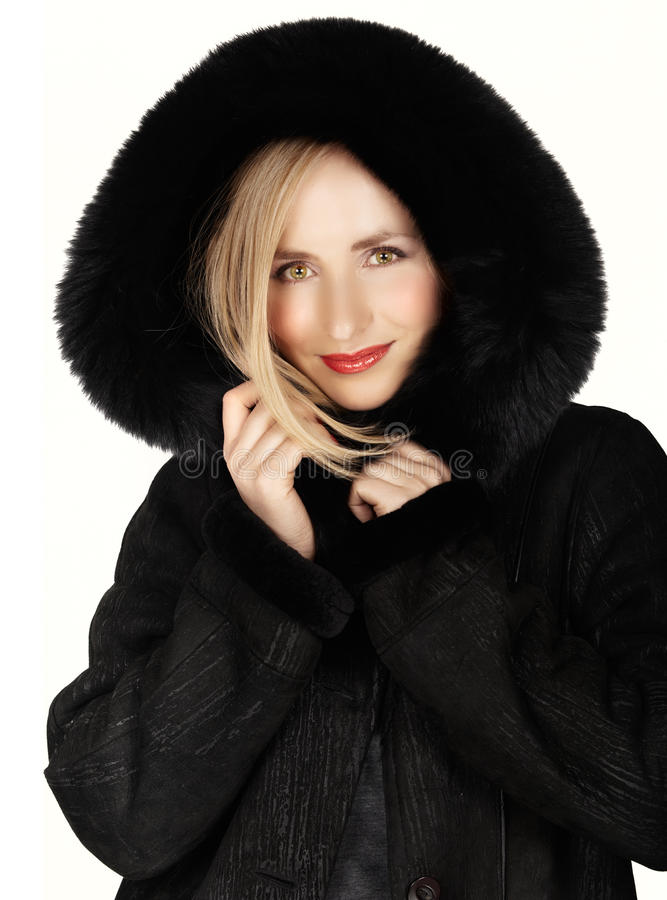 Woman in winter fur coat. Young beautiful woman happy in her winter black fur coat on white background royalty free stock photos