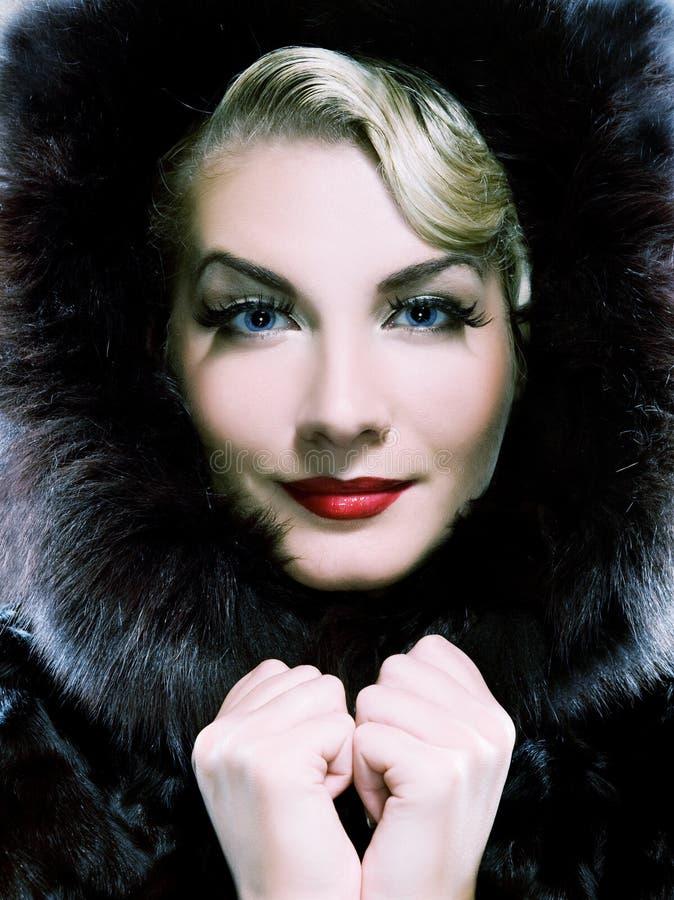 Woman in winter fur coat. Beautiful woman in winter fur coat. Toned in blue royalty free stock photo
