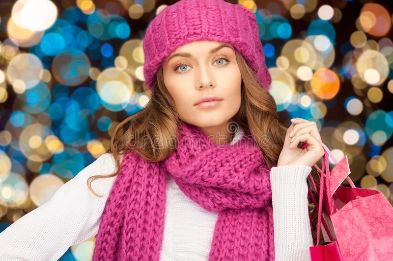 Woman in winter hat with christmas shopping bags. Sale, christmas, holidays and people concept - smiling woman in winter hat with shopping bags over lights royalty free stock photo