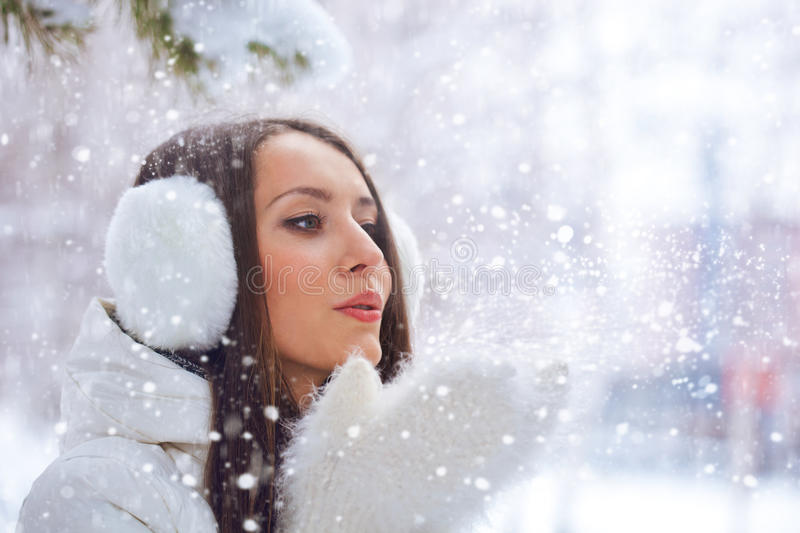 Woman in winter park blowing on snow stock images
