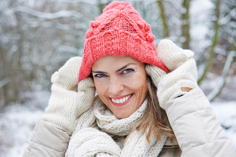 Woman in winter putting wool cap on stock photography