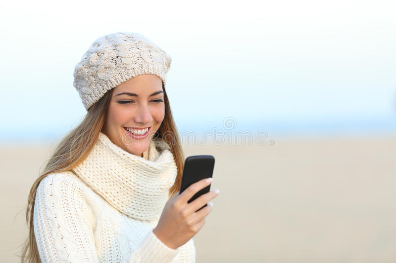 Woman in winter using a smart phone. Woman warmly clothed in winter using a smart phone on the beach royalty free stock images