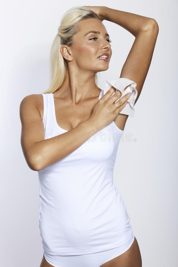 Woman wipes the armpit with wet wipes royalty free stock images