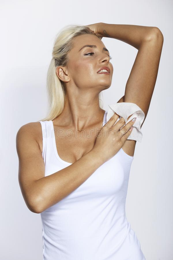 Woman wipes the armpit with wet wipes stock photos