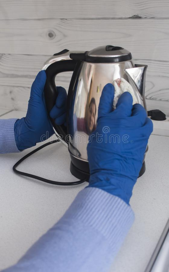 Woman wipes the kettle from the dirt with a rag stock photos