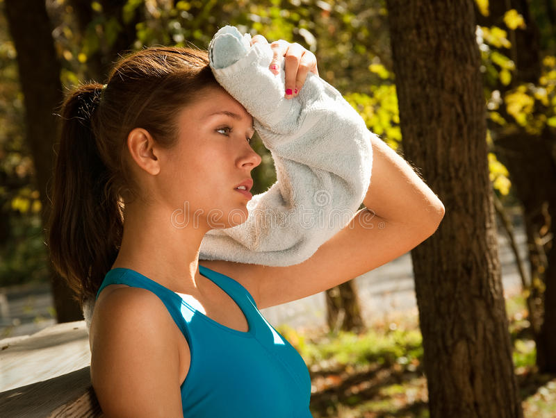 Woman wiping brow with towel royalty free stock image