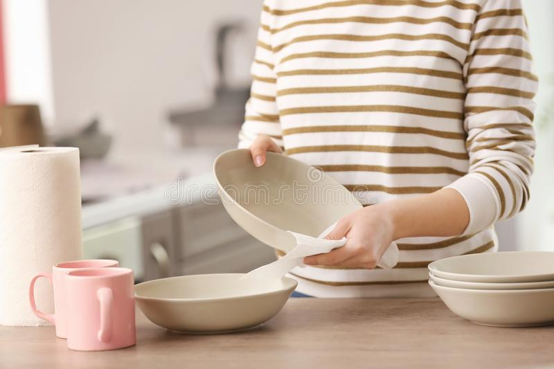 Woman wiping dishware with paper towel. In kitchen royalty free stock photography