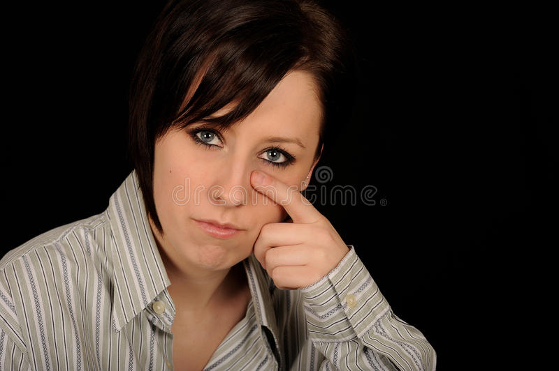 Woman wiping tears. Portrait of sad woman wiping tears with finger, black background stock photo