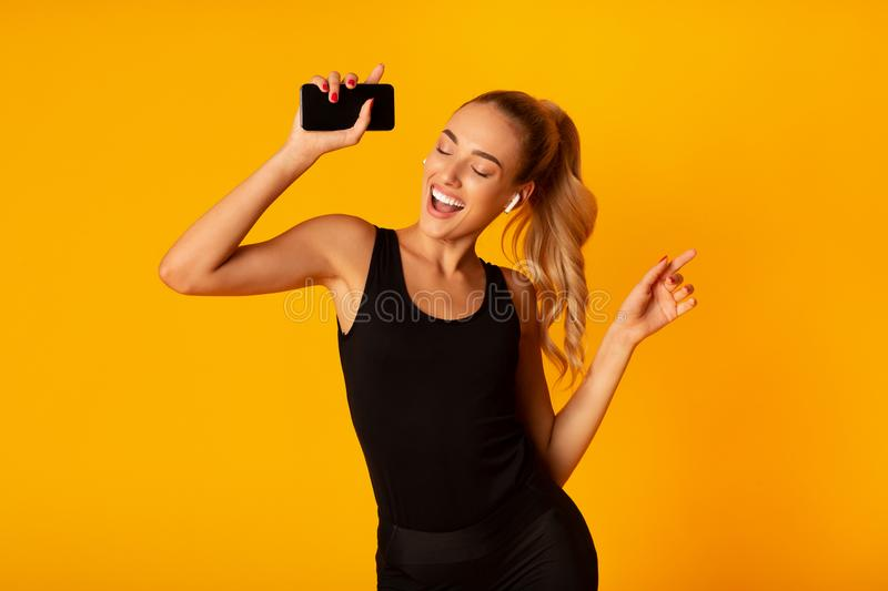 Woman In Wireless Earbuds Holding Smartphone And Dancing, Studio Shot. Music App. Sporty Woman In Wireless Earbuds Holding Smartphone And Dancing Over Yellow stock photos