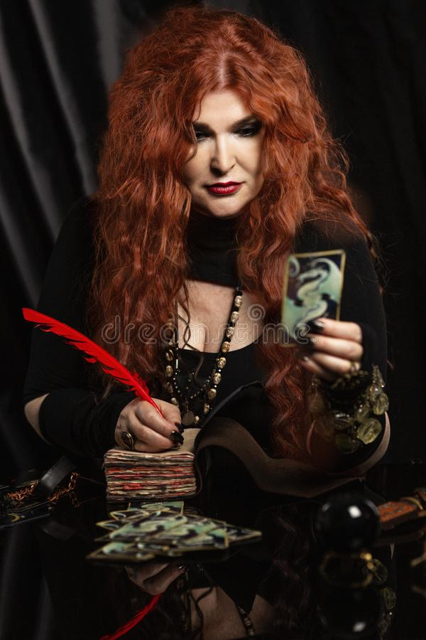 Woman witch, fortune teller with red hair performs a magical ritual. Card reading royalty free stock photography