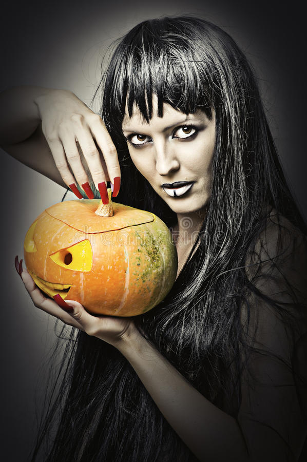 Woman witch holding pumpkin. Woman witch with black hair with pumpkin royalty free stock image