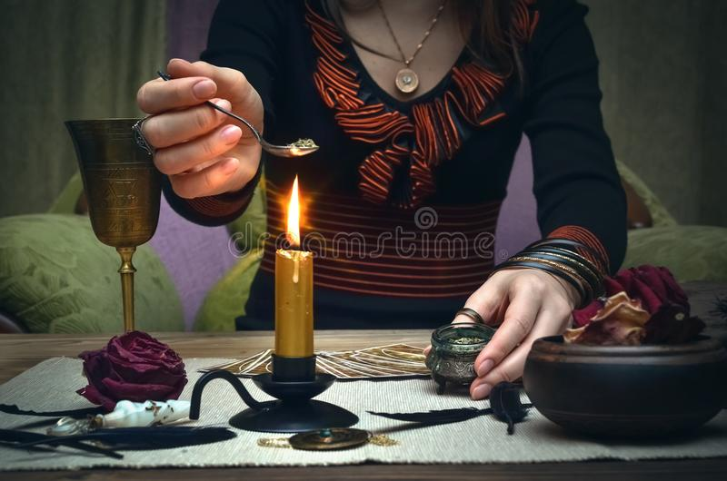 Woman witch prepare a magic potion. Tarot cards. Future reading. Fortune teller concept. royalty free stock photos