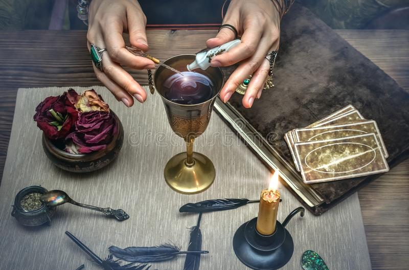Woman witch prepare a magic potion. Tarot cards. Future reading. Fortune teller concept. royalty free stock image