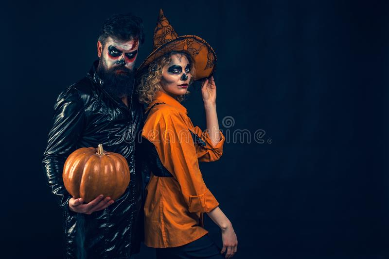 Woman witch with Pumpkin and Handsome bearded man. Enjoying nice Halloween together. royalty free stock photography