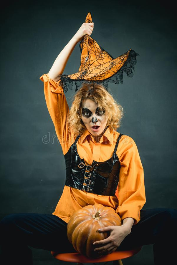 Woman witch with pumpkin. Young woman with witch hat dressed as vampire for Halloween party. Witch in magic hat. royalty free stock photos