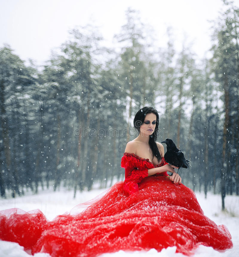 Woman witch in red dress with raven in her hand sits on snow in royalty free stock photos