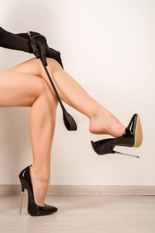 Free Woman With Whip In Black Fetish Shiny Patent Leather Stiletto High Heels With Ankle Strap Stock Photos - 173974023